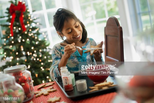 A young girl decorating Christmas cookies with icing. : Stock Photo