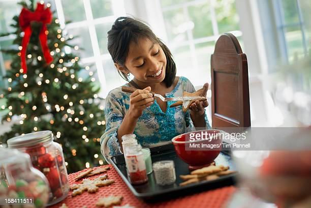 Una chica joven decorar galletas de Navidad con hielo.