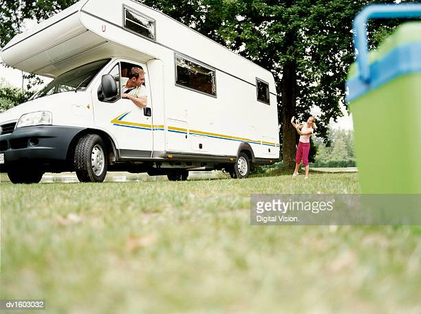 Young Girl Directing Her Father as he Reverses a Motor Home into a Parking Space in a Field