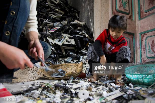 A young girl disassembles computer CD players March 23 2008 in Guiyu China Since the late 1980's ewaste from developed countries has been imported to...