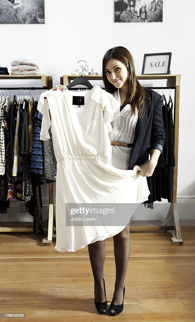 Young girl displaying white dress while shopping : Stock Photo