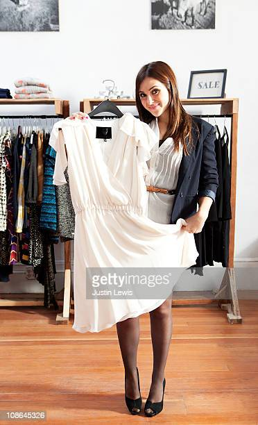 Young girl displaying white dress while shopping