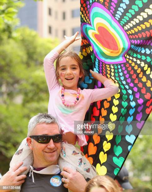 A young girl displays her support whilst sitting atop her fathers shoulders at the YES March for Marriage Equality on October 21 2017 in Sydney...