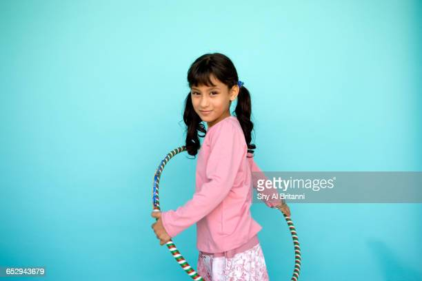 A young girl doing a hula hoop.