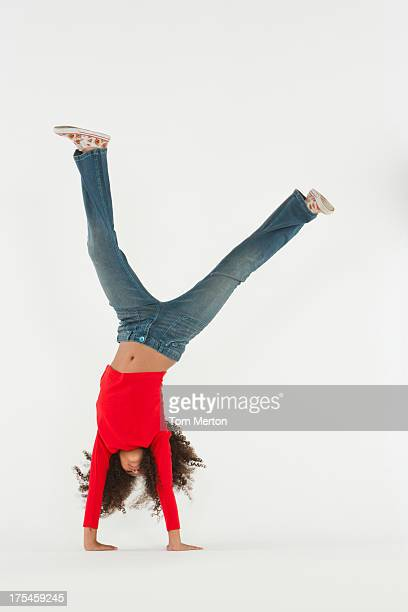 Young girl doing cartwheel indoors