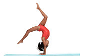 young girl doing gymnastics with motion blur on blue mat