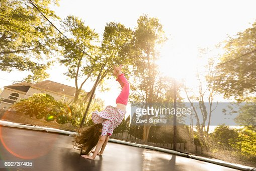 Young girl doing handstand on large trampoline, low angle view