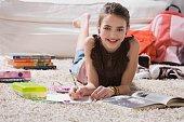 Young girl doing homework on floor