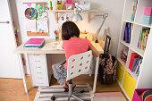 School girl doing homework at home in her desk. Back view.