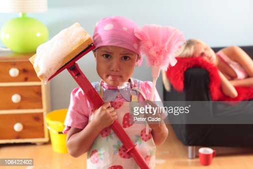 young girl doing housework, mother asleep on sofa : Stock Photo