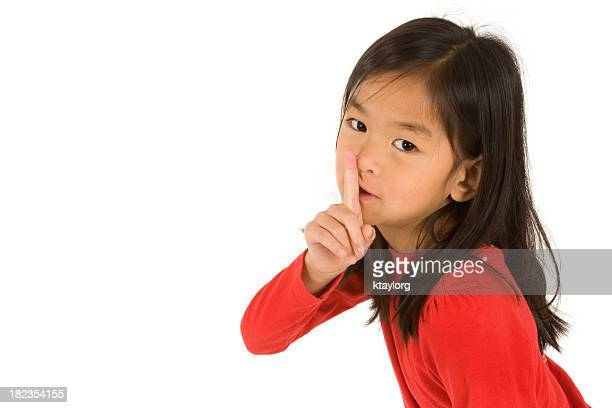 Young girl doing the be quiet sign with her hand