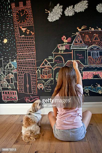 Young girl drawing on a blackboard