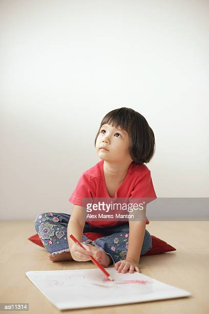 Young girl drawing on drawing pad, looking up