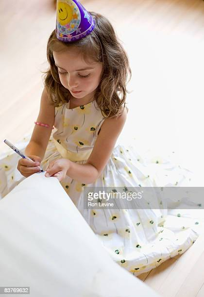 Young girl drawing on paper at a birthday party
