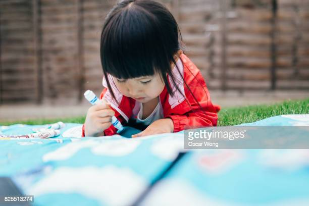 Young girl drawing on sheet in graden