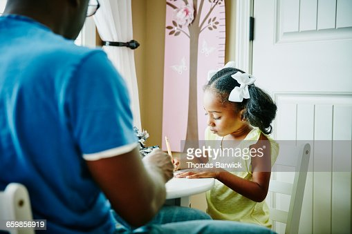 Young girl drawing with father at table : Stock Photo