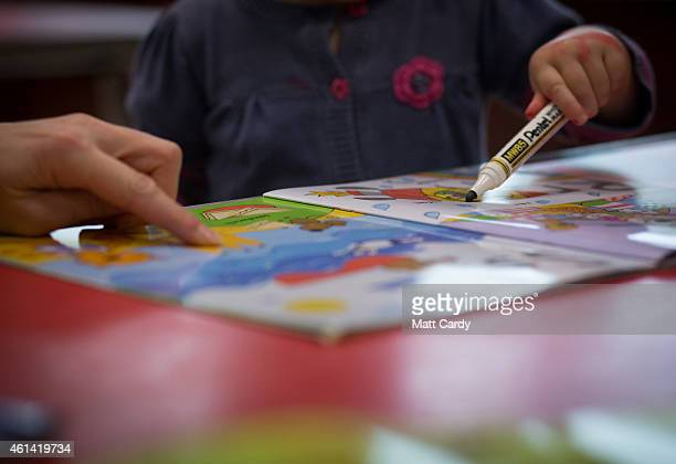 A young girl draws at a playgroup for preschool aged children in Chilcompton near Radstock on January 6 2015 in Somerset England Along with the...