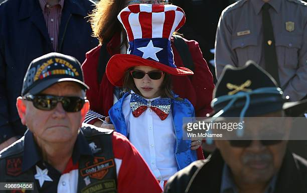 A young girl dressed in an Uncle Sam outfit attends a Veterans Day ceremony at the National World War II Memorial November 11 2015 in Washington DC...