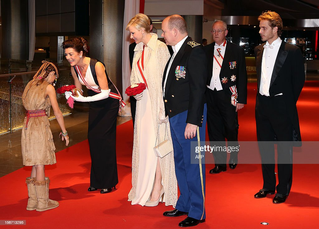 A young girl dressed like an Indian squaw offers a bunch of flowers to Princess Caroline of Hanover (L) as Prince Albert II of Monaco (R, foreground), his wife Charlene of Monaco (C), Andrea Casiraghi (R), their nephew, look on as they arrive to attend the Monaco National Day gala evening at the Grimaldi Forum in Monte Carlo, on November 19, 2012. AFP PHOTO POOL SEBASTIEN NOGIER