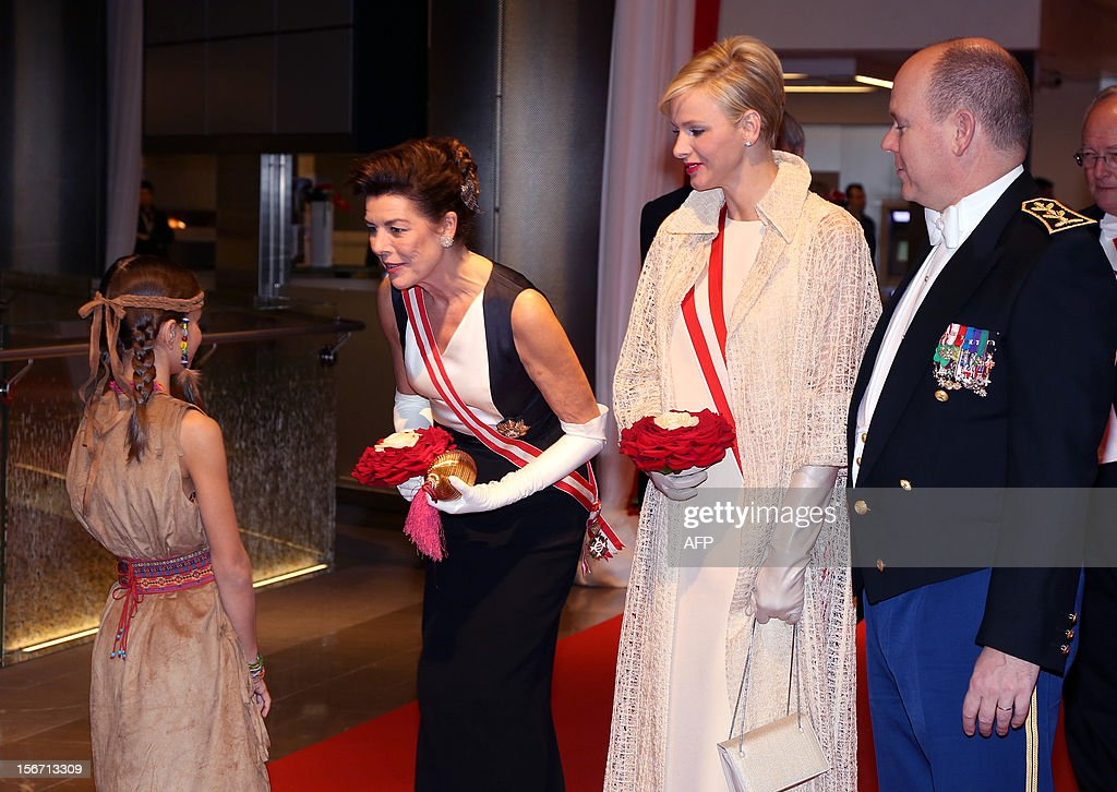 A young girl dressed like an Indian squaw offers a bunch of flowers to Princess Caroline of Hanover (L) as Prince Albert II of Monaco (R) and his wife Charlene of Monaco (C) look on as they arrive to attend the Monaco National Day gala evening at the Grimaldi Forum in Monte Carlo, on November 19, 2012.