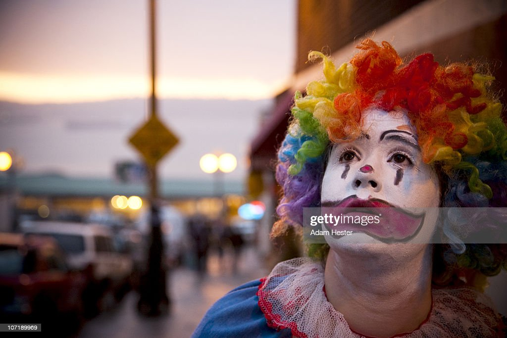 A young girl dressed up as a clown.