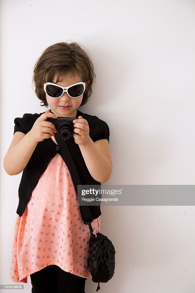 A young girl dressed up, playing with a camera : Stock Photo