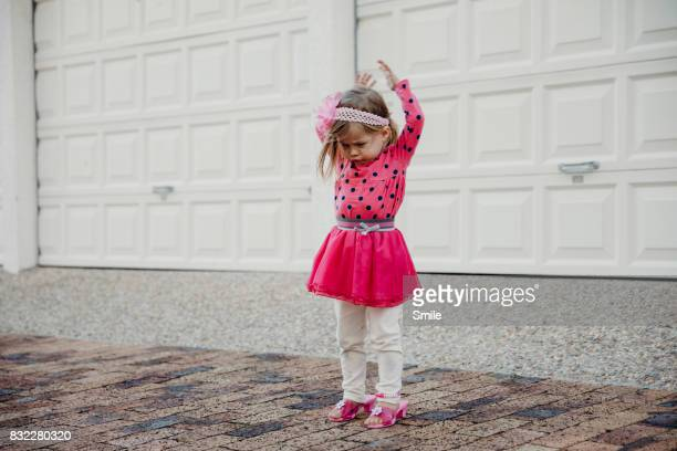 Young girl dressed up with arms in the air