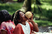 A young girl drinking coconut milk.
