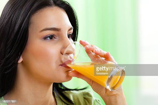 Young girl drinking fresh orange juice