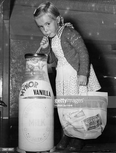 A young girl drinking from an outsize bottle of milk at the 1950 Royal Easter Show in Sydney carrying a bag advertising Cadbury's chocolate