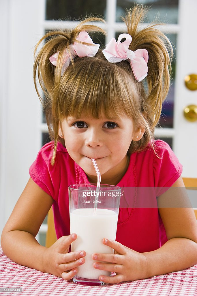 Young girl drinking milk with a straw on a table : Stock Photo