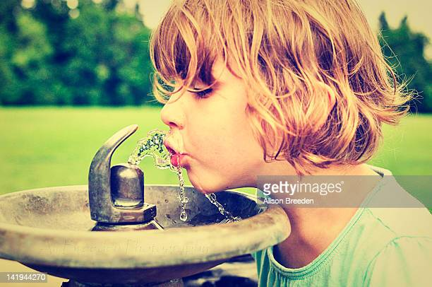 Young girl drinking water from fountain