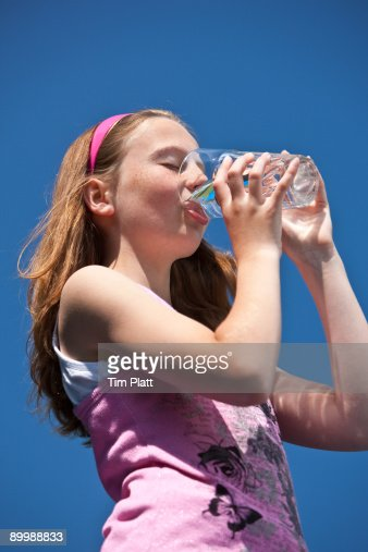 Young girl drinking water outdoors. : Stock Photo