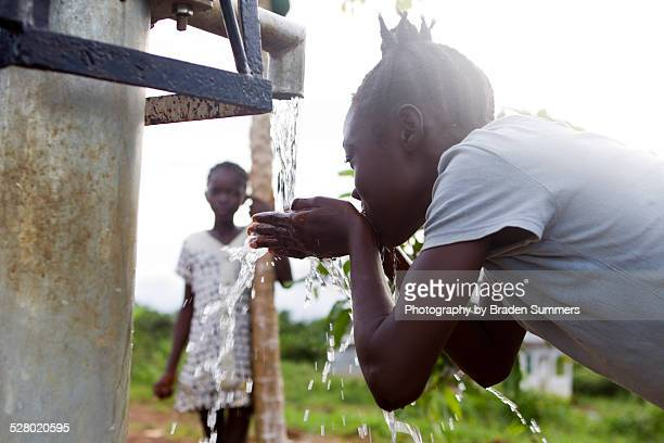 Young girl drinks clean water from well