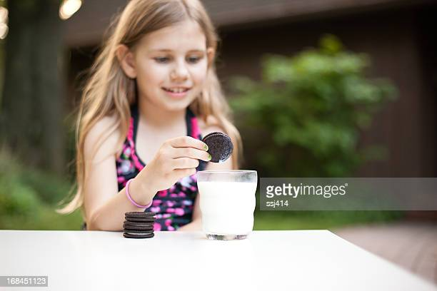 Young Girl Dunking Her Cookie in Milk