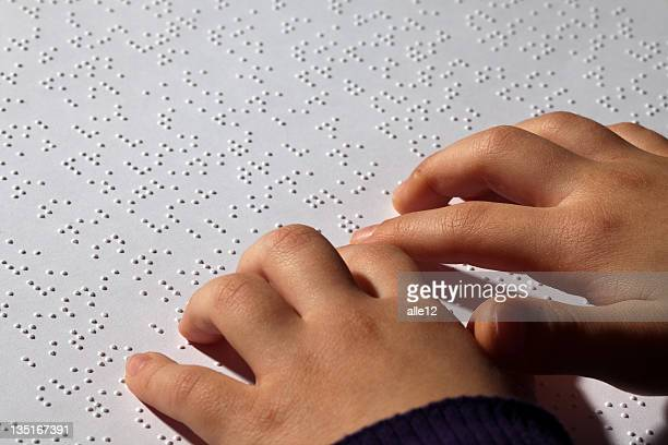 Young girl eading braille