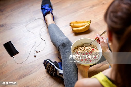 Young girl eating a oatmeal with berries after a workout . Fitness and healthy lifestyle concept. : Stock Photo