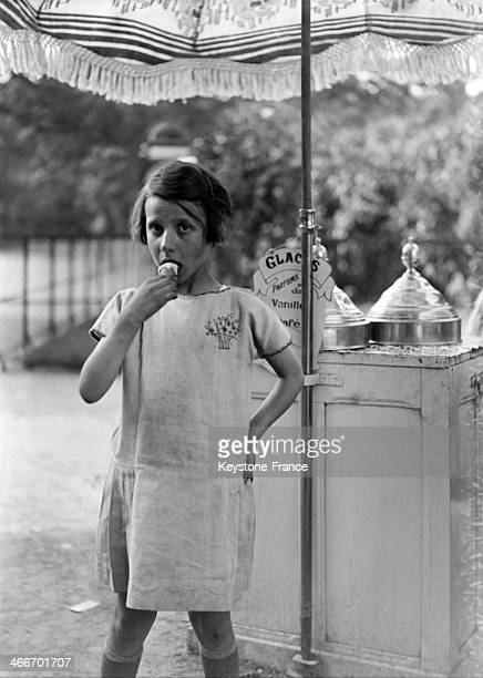 Young girl eating an ice cream during summer time in 1929 in Paris France