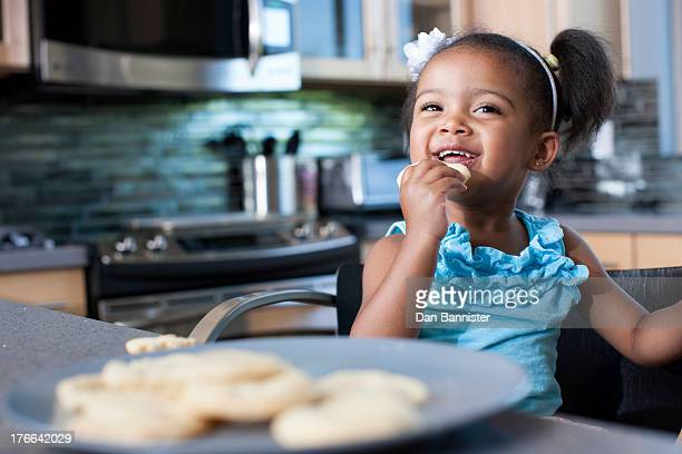 Young girl eating biscuits