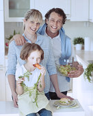 Young girl eating carrot with parents