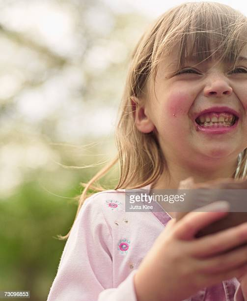 Young girl eating chocolate Easter egg and laughing