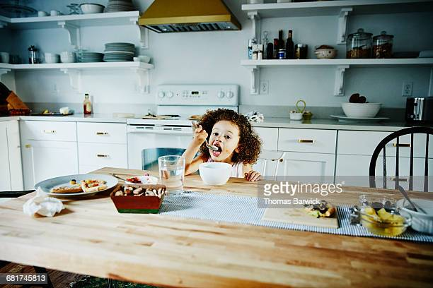 Young girl eating ice cream at kitchen table
