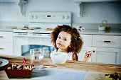 Young girl eating ice cream in kitchen