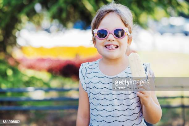 Young girl eating ice-cream in summer in park