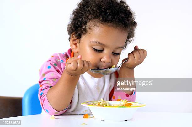 Young girl eating out of a bowl using two spoons at once