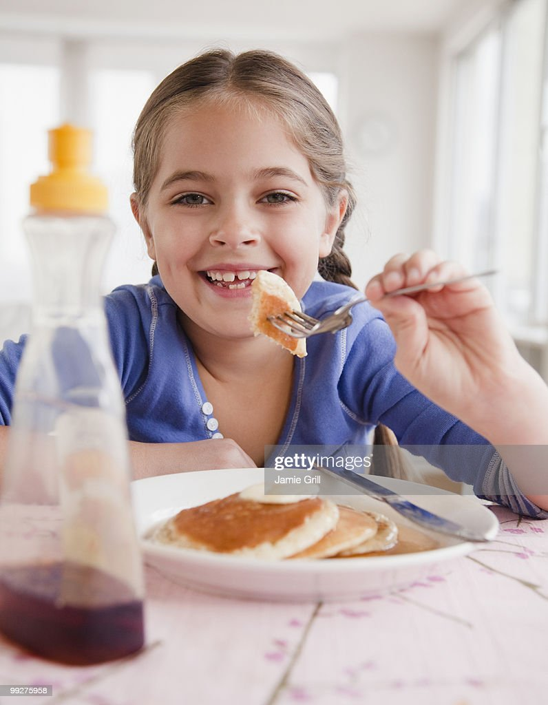 Young Girl Eating Pancakes Stock Photo | Getty Images