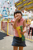 Young girl eating popcorn at the fair