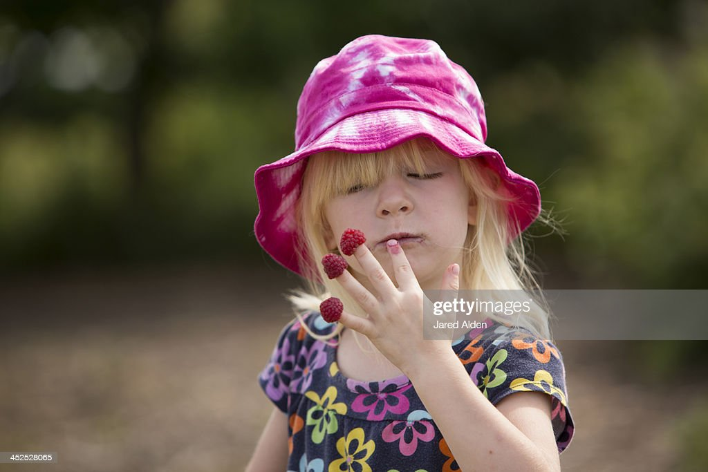 Young girl eating red raspberries on her fingers : Stock Photo