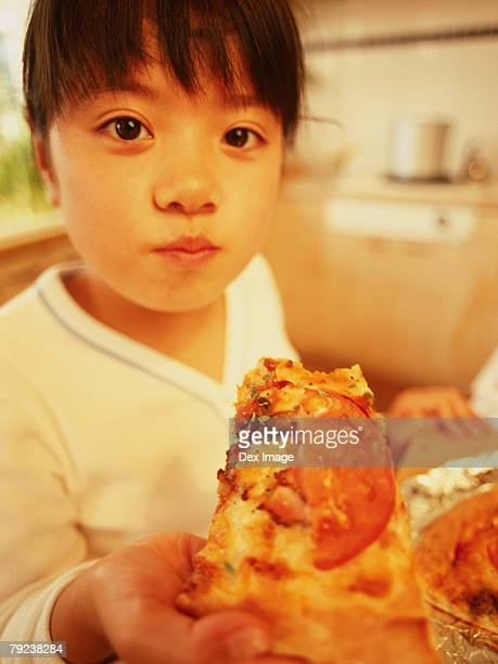 Young girl eating slice of pizza, close-up