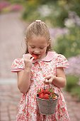 Young girl eating strawberry from pail outdoors